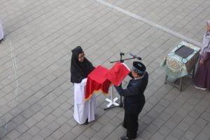 Pembina Upacara menyerahkan Bendera Merah Putih Kepada Petugas pengibar bendera